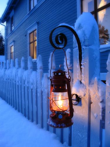 Öllampe am winterlichen Gartenzaun