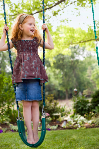 Girl standing on swing
